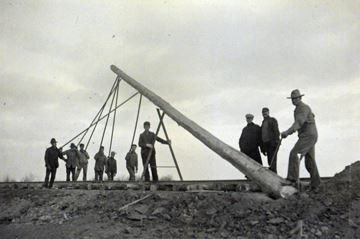 Workers Erect Pole