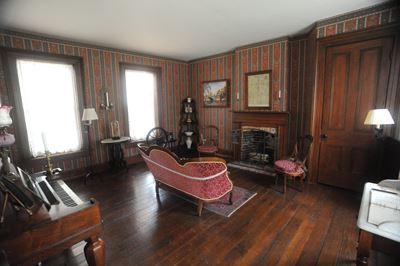 The Living Room inside the Jones House features a wood floor and historic furniture.