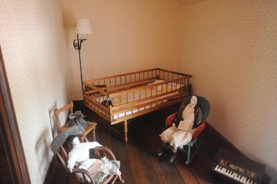 A baby bed and dolls sit in a corner of the Historic Jones House.