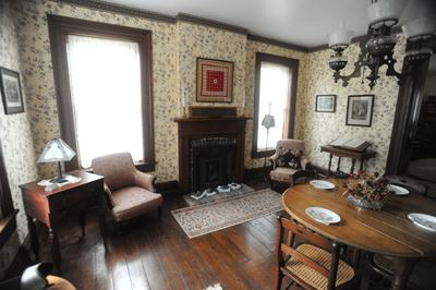 A sitting room furnished with antique furniture and walls adorned with wallpaper make up the dining