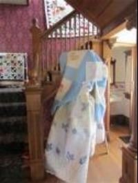 A blue and white quilt leans against the stairs in the Yost House.