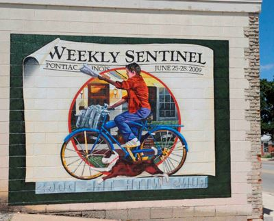 A mural of a paperboy on a bicycle, celebrating the Pontiac Weekly Sentinel